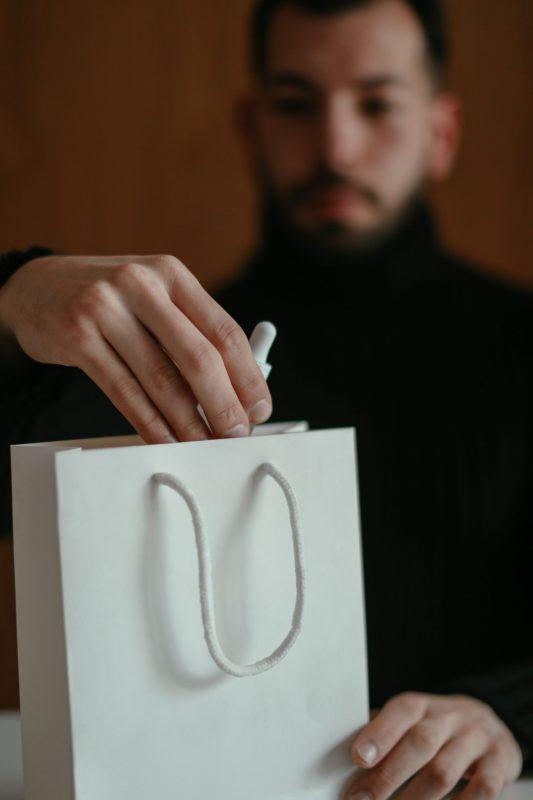 גבר מטופח מחזיקת שקית מוצרי יופי